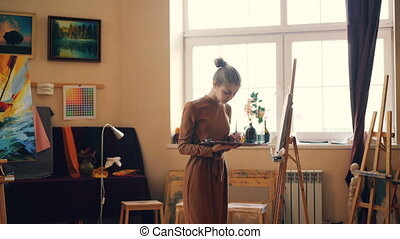 Cute young woman painter is working in studio holding...