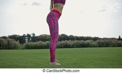 Cute young woman practicing squats in park