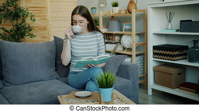 Cute young woman reading book and drinking tea indoors in...