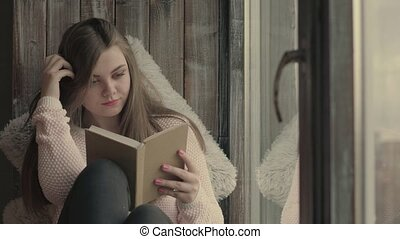 Cute young woman reading book