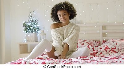 Cute young woman relaxing at home at Christmas sitting on...