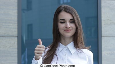 young woman showing thumbs up and smiles