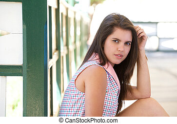 Cute young woman sitting outdoors in summer