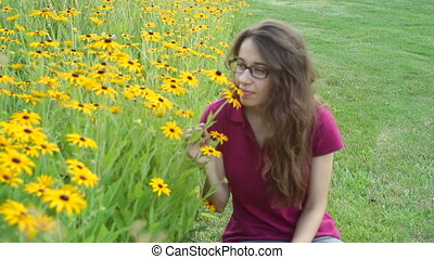 Cute young woman smelling yellow flowers on a flowerbed in the park