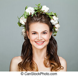 Cute young woman smiling, closeup portrait. Female Model Face with Cotton Flowers