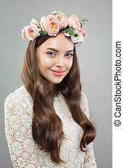 Cute young woman smiling. Pretty model girl with clear skin, long curly hairstyle and flowers crown