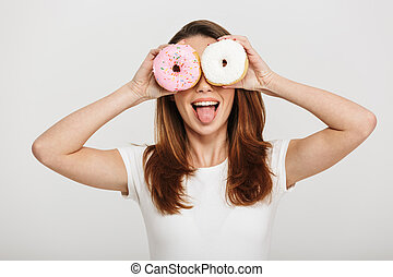 Cute young woman standing holding donuts in front of eyes.