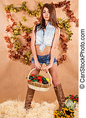 Cute young woman staying in a hay with a bucket of vegetables