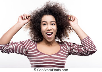 Cute young woman touching her curly hair