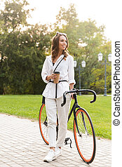 Cute young woman walking in park with bicycle holding coffee.