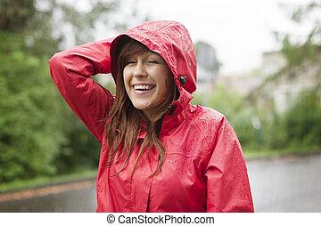 Cute young woman walking through the rain