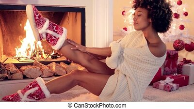Cute young woman warming herself at the fire in festive red...