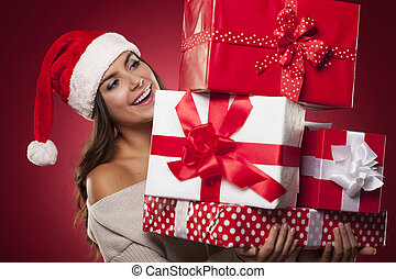 Cute young woman wearing santa hat holding christmas gifts