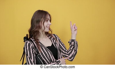 Cute Young Woman With Bag Light Brown In Striped Pink, Black Shirt On A Yellow Background, Happy Girl Smiling, Brought Forefinger Back Up. Concept Of New Ideas, Smart People