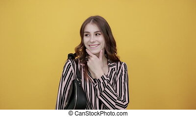 Cute Young Woman With Bag Light Brown In Striped Pink, Black Shirt On A Yellow Background, Happy Girl Smiles And Holds Her Chin With Hand. The Concept Of People Who Think