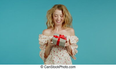 Cute young woman with blonde hair holding gift box with bow, she wonders what is inside. Blue wall background. Girl smiling, she is happy to get present