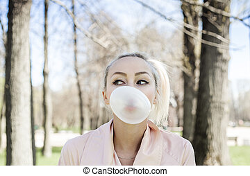 Cute young woman with bubble chewing gum outdoors, lifestyle portrait