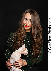 Cute Young Woman with Cat on Black Background