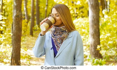 Cute young woman with cup of coffee in the autumn park