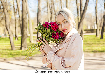 Cute young woman with flowers outdoors. Female model with peony portrait