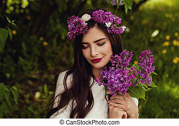Cute young woman with summer flowers outdoors