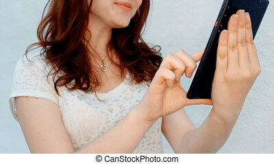 Cute young women having fun while browsing a tablet outside