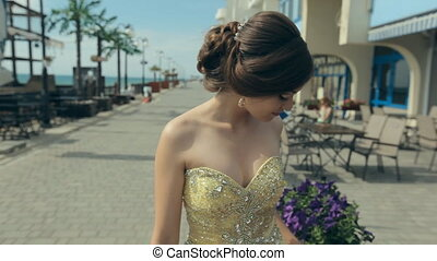 Cute young women in lemony long strapless dress touch bright flowers