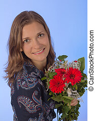 Cute young women with flowers over blue backgroung