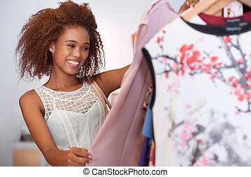 Attractive young woman with curly hair browsing through clothes hanging on racks while standing in a clothing shop