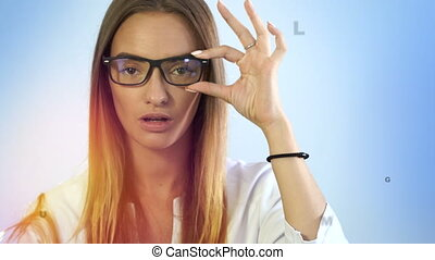 Cutie young blonde lady checks her vision with virtual letters in the air