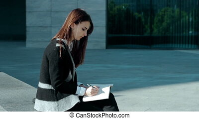 cutie woman make notes in a book outdoors