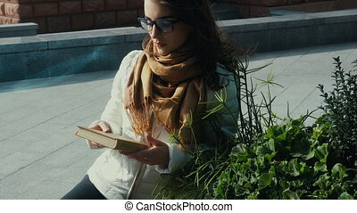 cutie young brunette woman in glasses reading a book