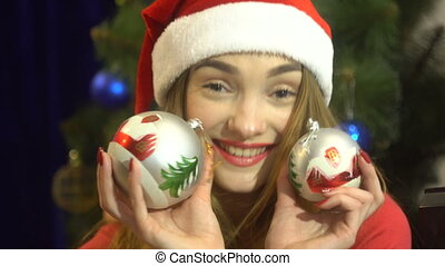 cutie young girl in santa hat with christmas toys in hands looking at the camera and smiling