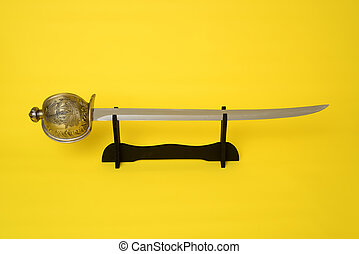 Cutlass on stand blade, guard, and hilt isolated over yellow