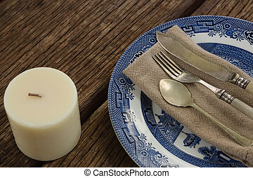 Cutlery and napkin on plate with candle - Close-up of...