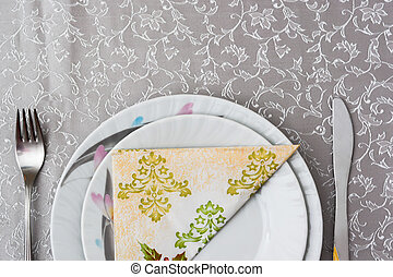 cutlery and plates with napkin on the table