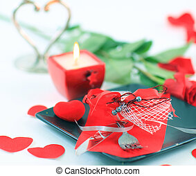 cutlery on dark plate with a candle decorated for...