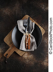 Cutlery on the plate on dark brown background.