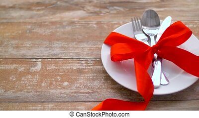 cutlery tied with red ribbon on plate - valentines day and...