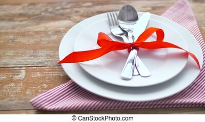 cutlery tied with red ribbon on plate - valentines day,...