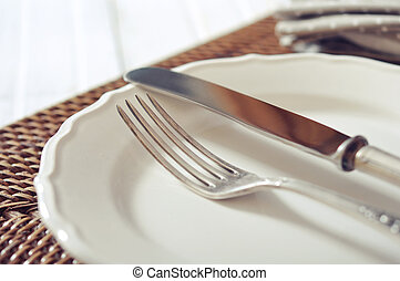 Cutlery - White plate, fork and knife on wicker wooden ...