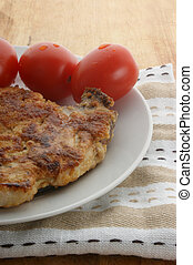 cutlet with organic tomato on a white plate