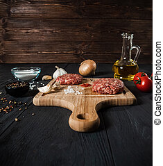Cutlets from minced meat with the ingredients on the black wooden table.