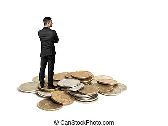 Cutout businessman with folded arms standing on a copper heap of ruble coins