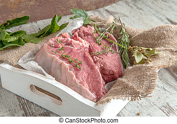 Cuts of beef for grilling on a wooden cutting Board with spinach, rosemary and Provencal herbs for the marinade in a rustic style