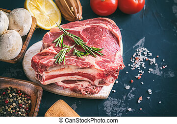 Cuts of beef for grilling on a wooden cutting Board with the Bay leaf, rosemary, olive oil and Provencal herbs for the marinade in a rustic style.