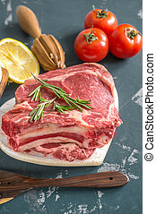 Cuts of beef for grilling on a wooden cutting Board with the Bay leaf, rosemary, olive oil and Provencal herbs for the marinade in a rustic style