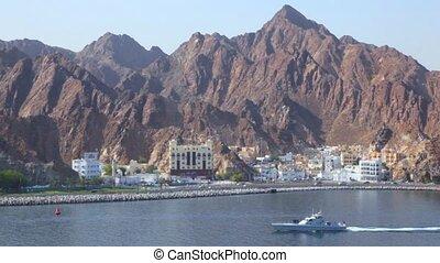 cutter sailing against seashore city Muscat, Oman