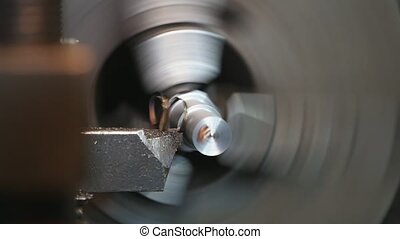 Cutter taking flakes from a metallic rod fixed to a lathe...