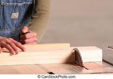 A female woodworker cross cuts apiece of pine.